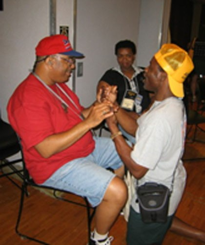 Du žmonės bendrauja taktiline gestų kalba