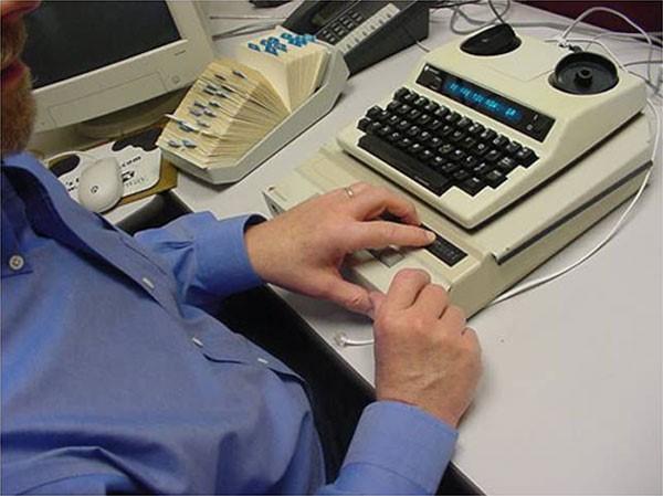 Kurčneregys skambina naudodamasis tekstofonu su Brailio eilute